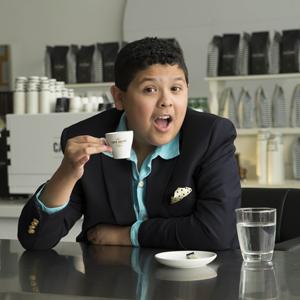 Мальчик пьет кофе