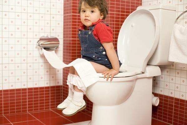 Ребенок сидит на унитазе