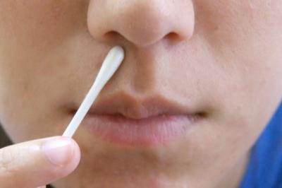 Смазывает нос ватной палочкой