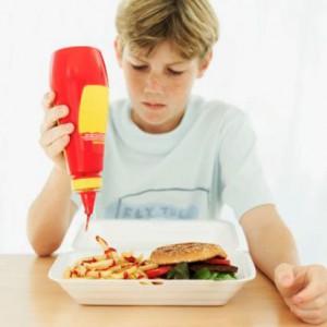 Мальчик ест фастфуд