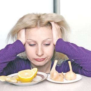 Девушка смотрит на чеснок и лимон