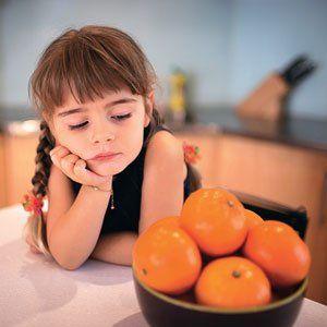 Девочка смотрит на апельсины