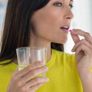 Девушка пьет таблетки