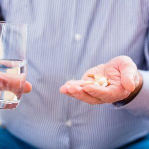 Мужчина пьет таблетки