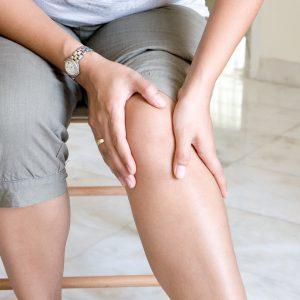 Девушка трогает колено