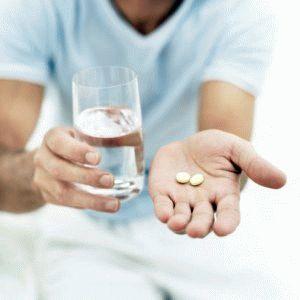 Таблетки и вода в руках у мужчины