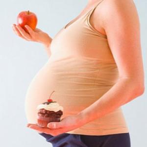 Беременная с пирожным и яблоком